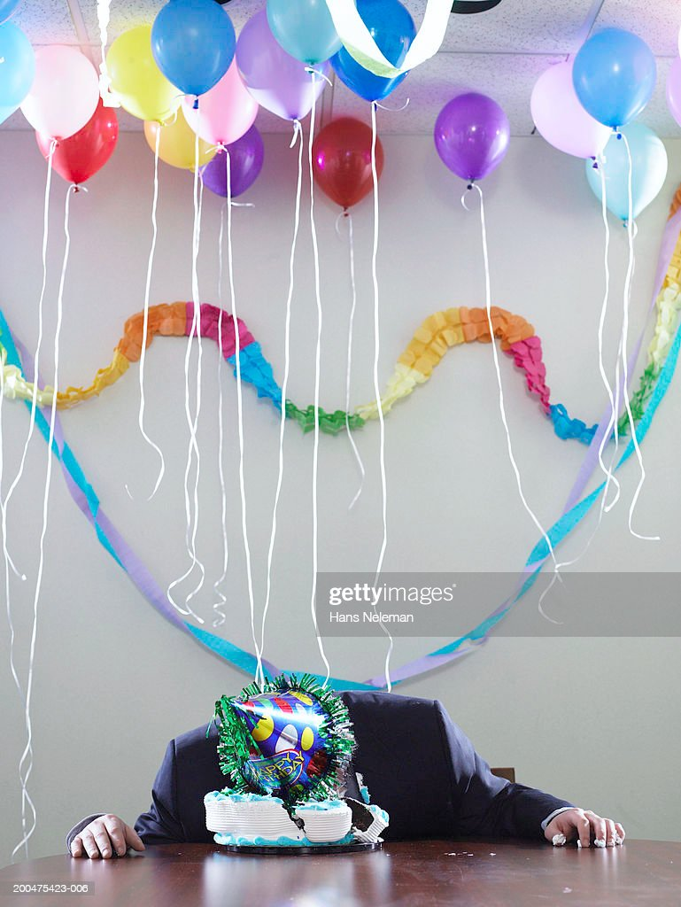 Businessman with face in birthday cake : Stock Photo
