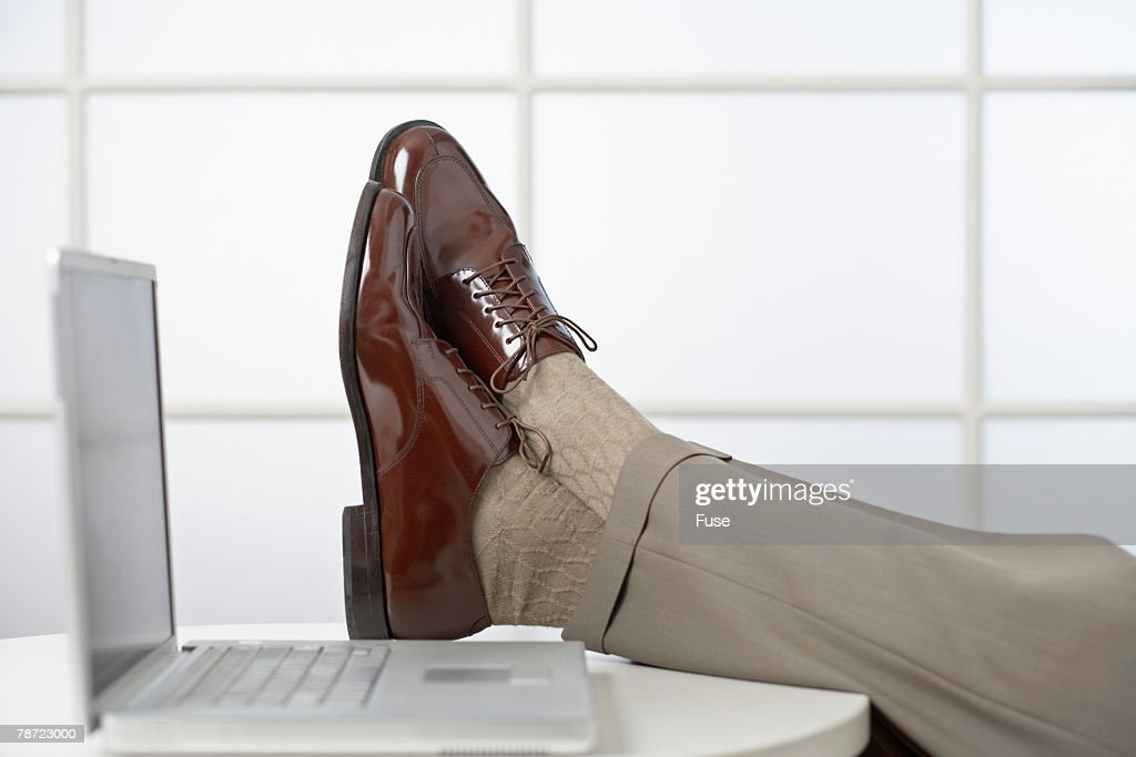 Businessman with Feet Up near Laptop
