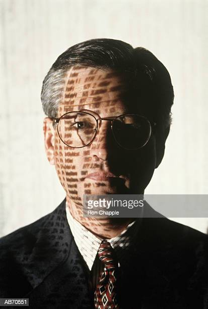 Businessman with financial news shadows on face