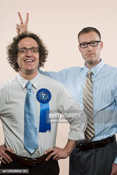Businessman with first place rosette and another man gesturing, close-up