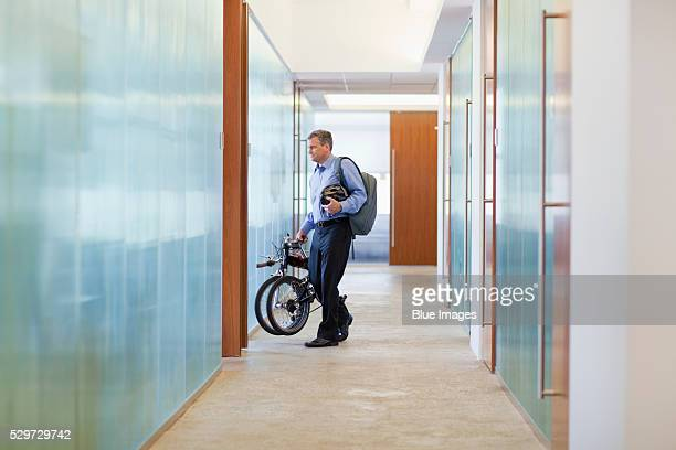 Businessman with folded bike in office hallway