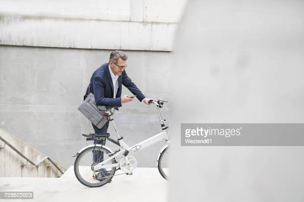 Businessman with folding bicycle looking at cell phone