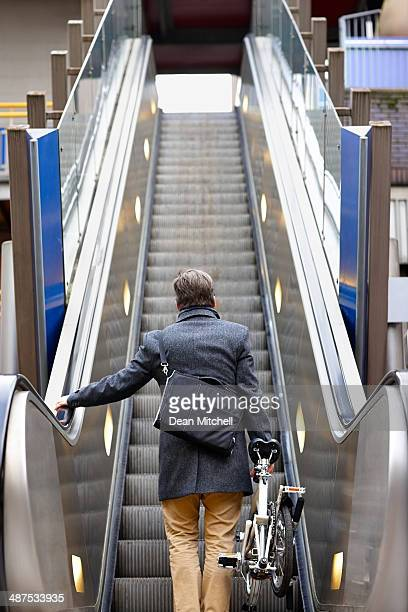 Businessman with folding bicycle on escalator