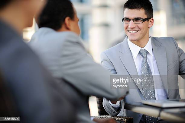 Businessman with glasses shakes colleague's hand