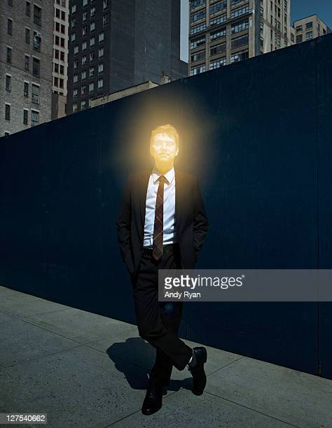 Businessman with glowing head in city.