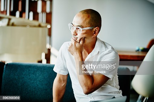 Businessman with hand on chin listening