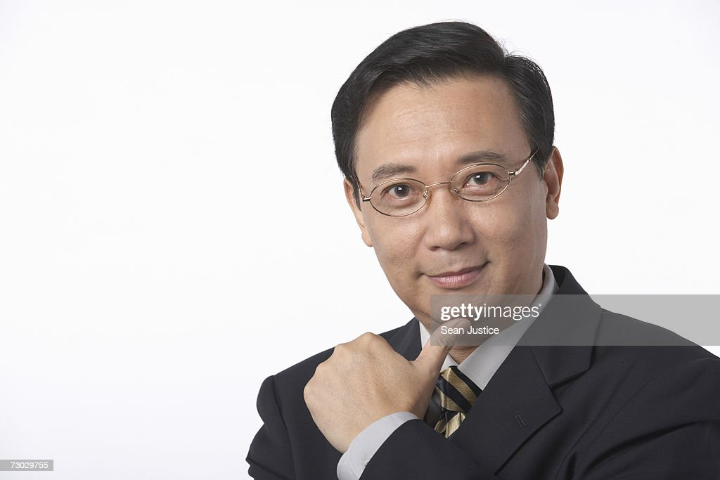 Businessman with hand on chin, portrait : Stock Photo