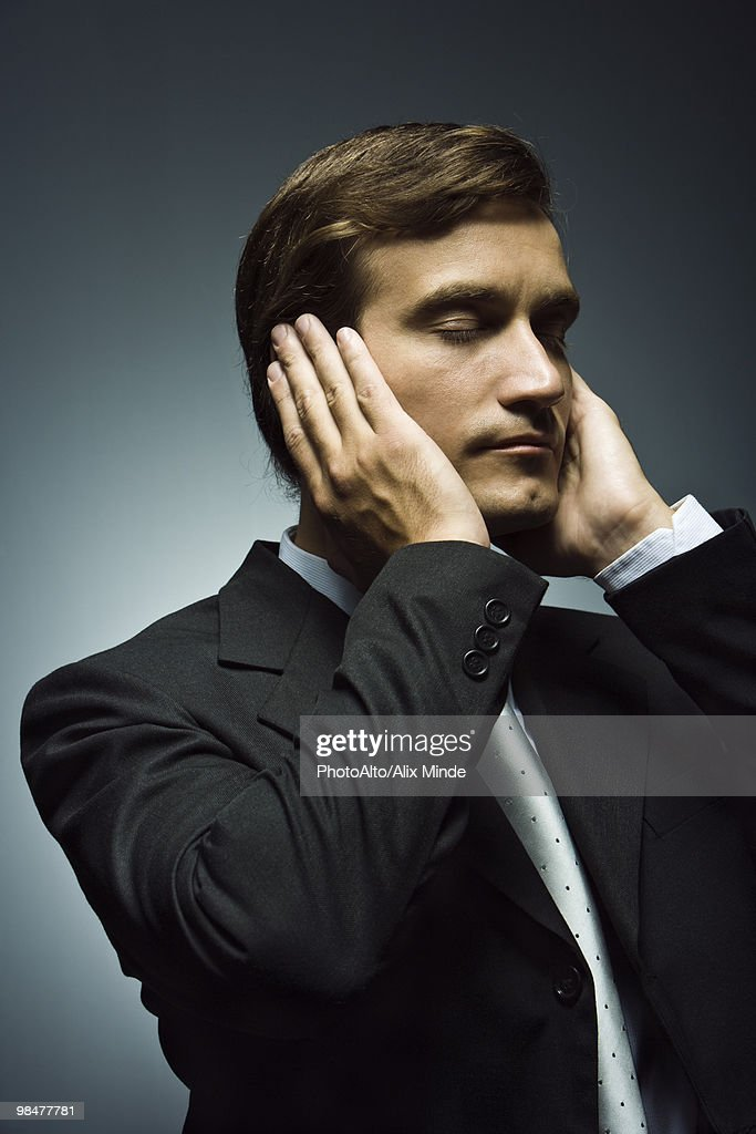 Businessman with hands covering ears and eyes closed