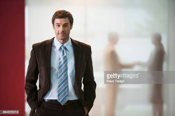 Businessman with hands in pockets in office