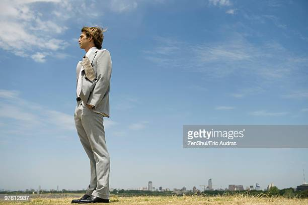 Businessman with hands in pockets standing in open field, city skyline on distant horizon