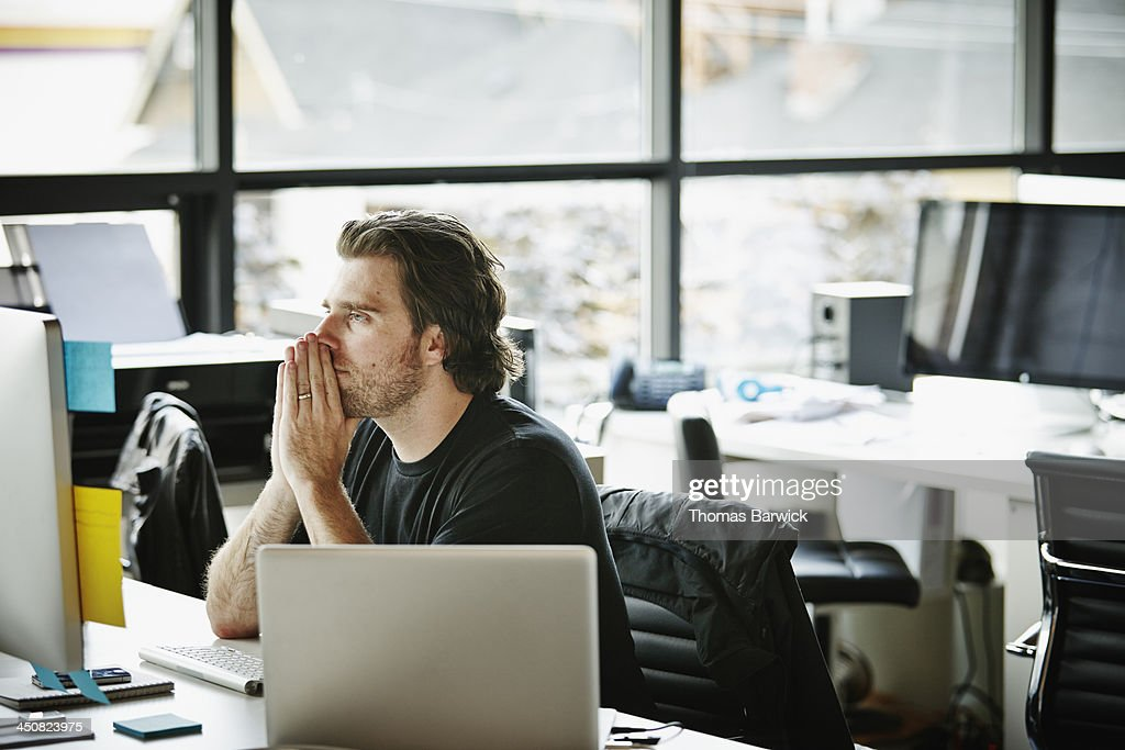 Businessman with hands on chin at workstation : Stock Photo