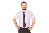 Young cheerful businessman standing with hands on waist and looking into camera, success concept. Isolated on white background