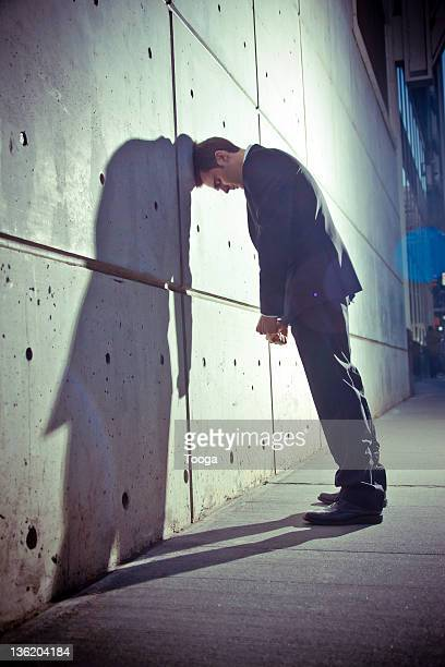 Businessman with head against wall at night
