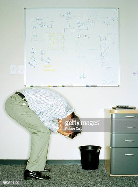 Businessman with head in hands in front of whiteboard, profile