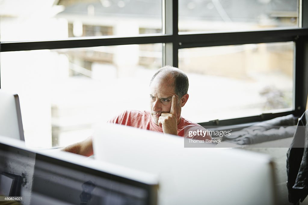Businessman with head on hand working on computer