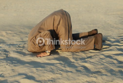Businessman with head stuck in sand at the beach : Stock Photo