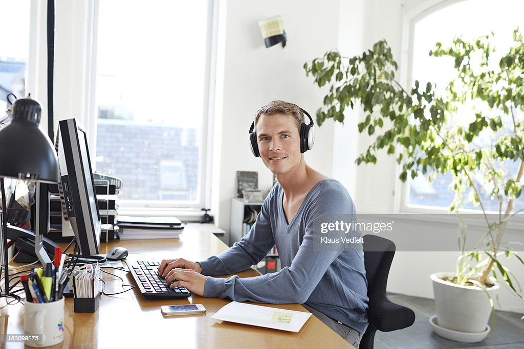Businessman with headphones sitting by desk : Stock Photo