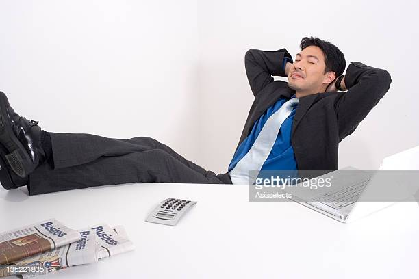 Businessman with his arms crossed behind his head day dreaming in an office