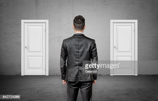 A businessman with his back turned stands between two identical closed white doors : Stock Photo
