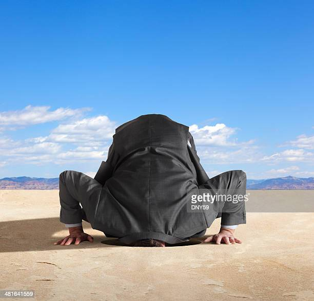 Businessman with his head in the sand