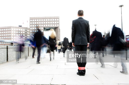 Businessman with his legs tied together in a crowd