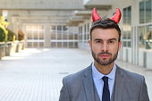 Businessman with horns close up.