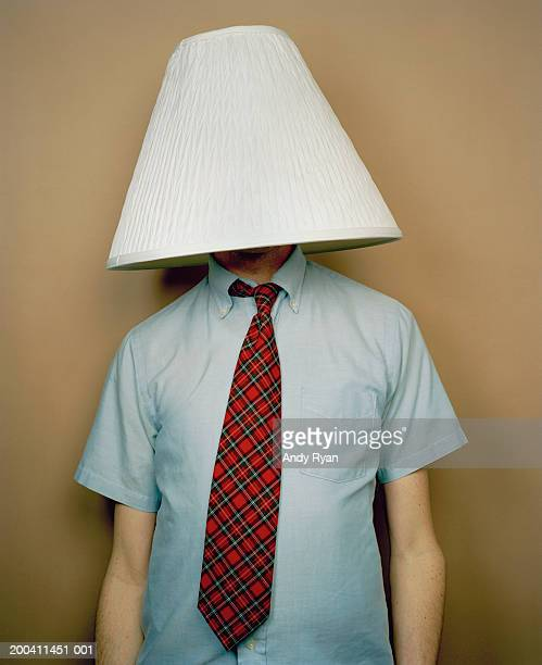 Businessman with lamp shade on head