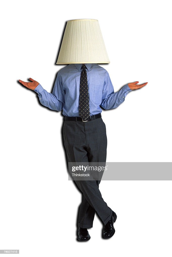 Businessman with lampshade on head, standing with hands held out, palms up. : Stock Photo