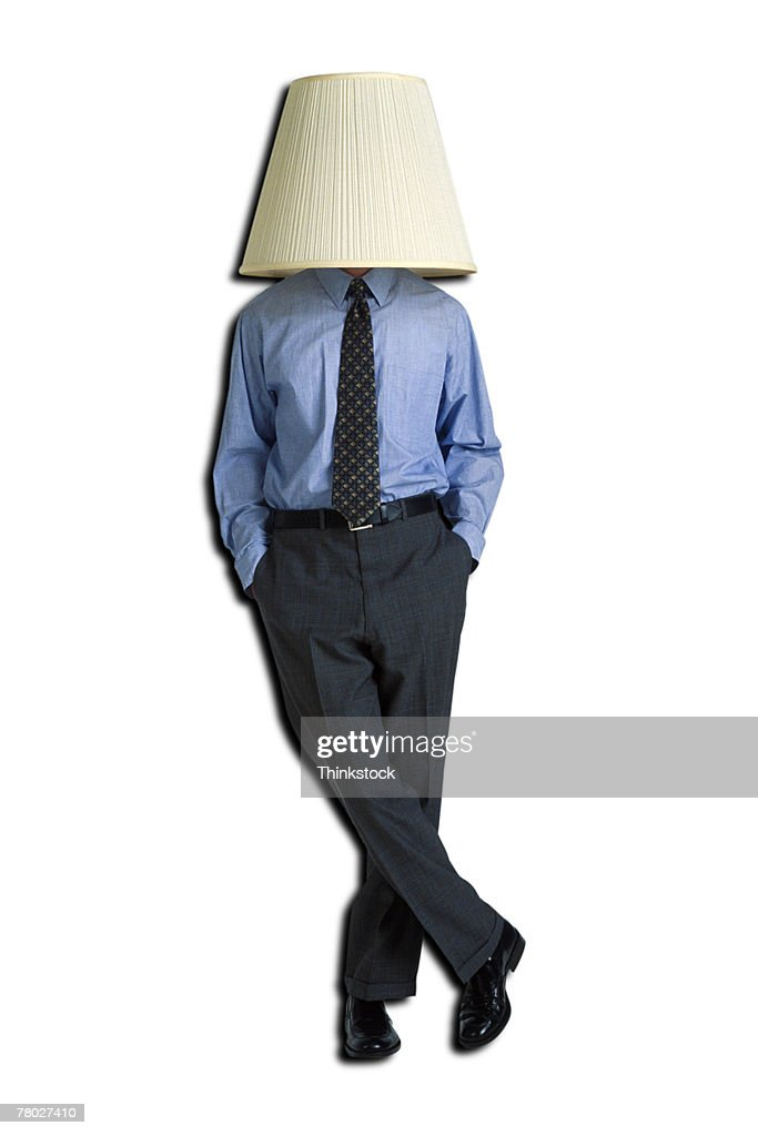 Businessman with lampshade on head, standing with hands in pockets. : Stock Photo