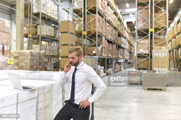Businessman with laptop and cell phone in warehouse