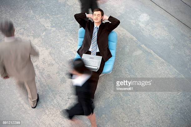 Businessman with laptop having a break with people passing by