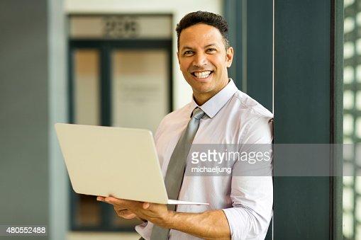 Hombre de negocios con ordenador portátil en oficina : Foto de stock