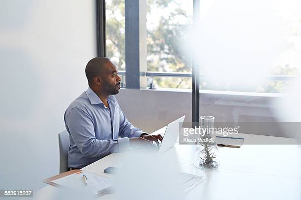 Businessman with laptop looking out of window