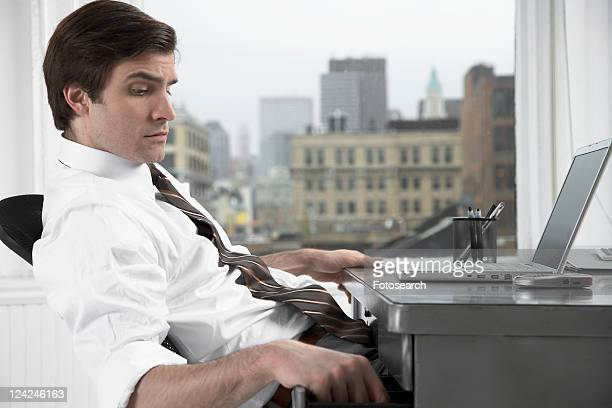Businessman with laptop opening desk drawer