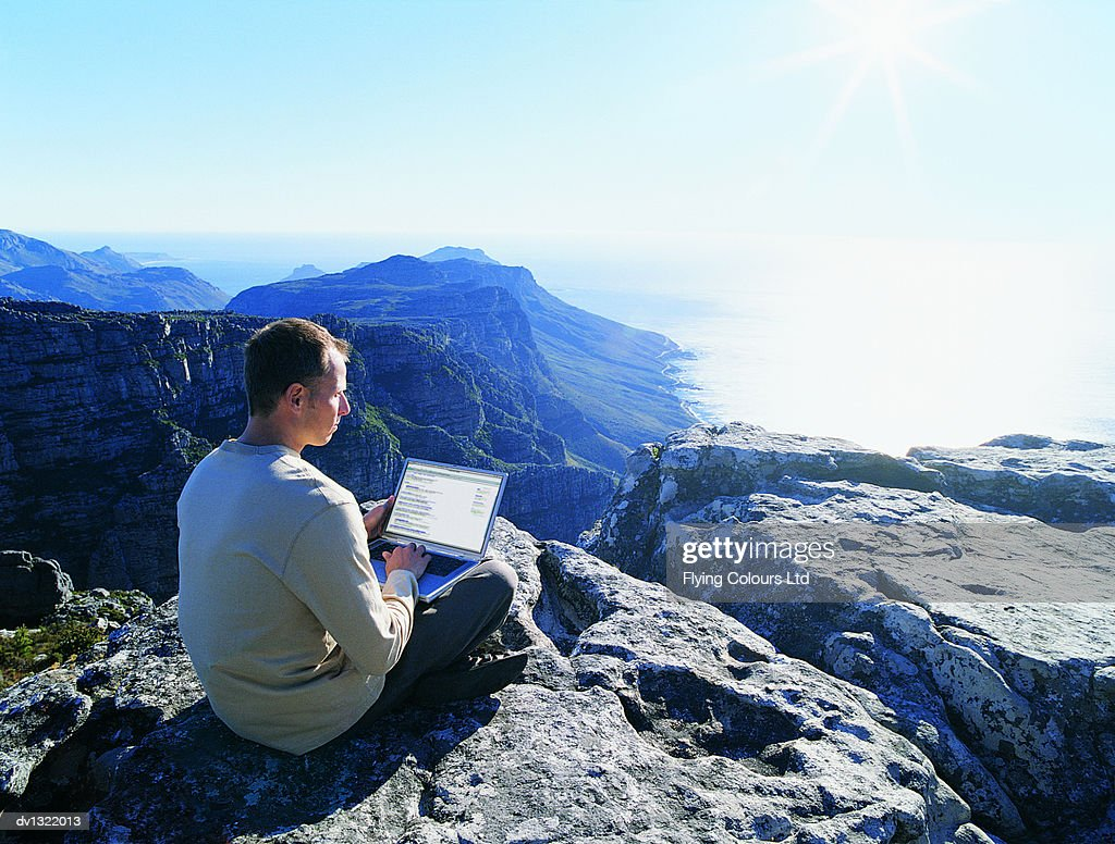 Businessman With Laptop Sitting Cross-legged on a Rock High Above the Sea : Stock Photo