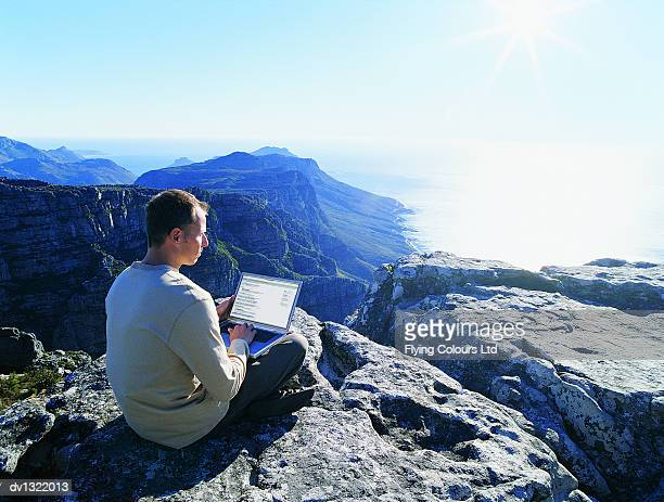 Businessman With Laptop Sitting Cross-legged on a Rock High Above the Sea