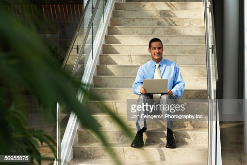 Businessman with laptop sitting on step : Stock Photo