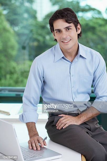 Businessman with laptop sitting on table (portrait)