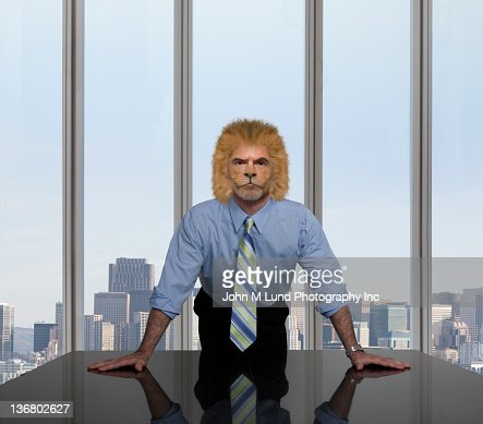 Businessman with lion's head leaning on table