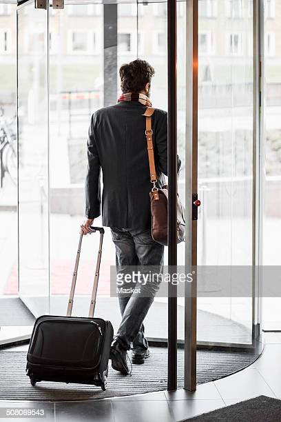 Businessman with luggage leaving hotel