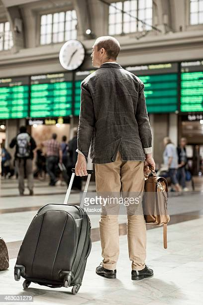 Businessman with luggage standing on railway station