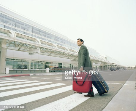 Businessman with luggages crossing road to airport : Stock Photo