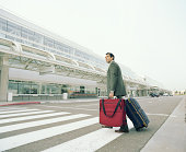 Businessman with luggages crossing road to airport