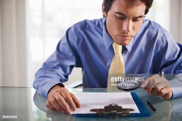 Businessman with magnifying glass reading small print