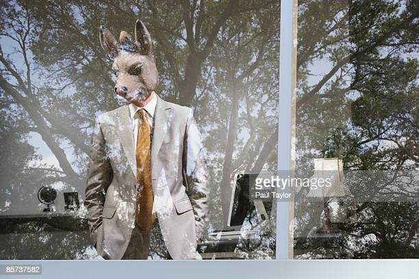 Businessman with mask in office with reflection