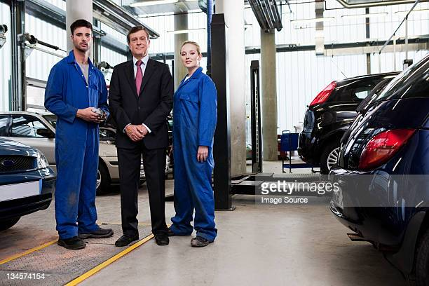 Businessman with mechanics in repair garage