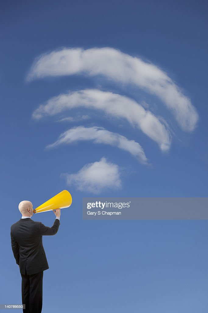 Businessman with megaphone lifted to wi-fi cloud : Stock Photo