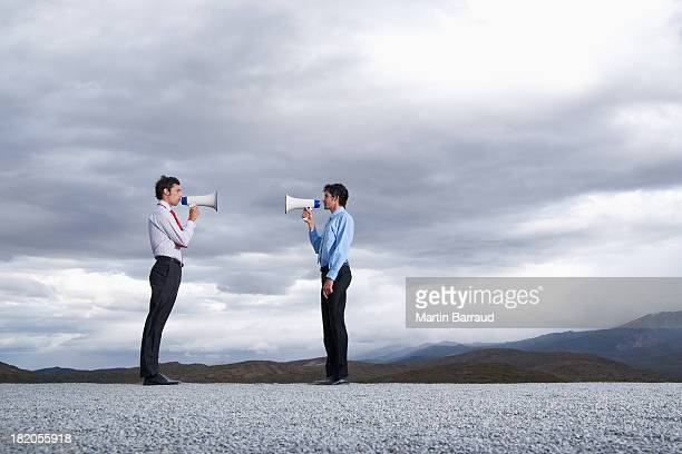 Businessman with megaphone  shouting face to face