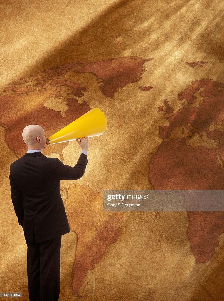 Businessman with megaphone speaking to world : Stock Photo