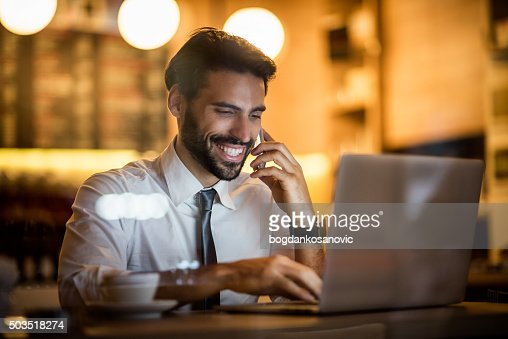 Businessman with mobile phone and laptop inside coffee shop